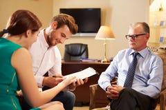年轻夫妇谈话与财政顾问在办公室 免版税库存照片