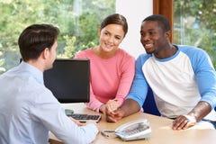 夫妇谈话与财政顾问在办公室 免版税库存图片