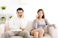 年轻夫妇谈话在电话 免版税图库摄影
