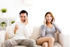 年轻夫妇谈话在电话 图库摄影
