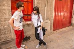 年轻夫妇谈话在街道上 免版税库存图片