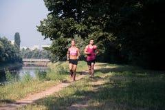 夫妇赛跑者连续城市公园 免版税库存图片