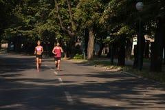 夫妇赛跑者连续城市公园 图库摄影