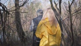 夫妇走在灰色森林人佩带的帽子的,太阳镜,背心 穿黄色外套的妇女 影视素材