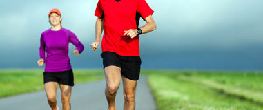 夫妇跑在乡下公路的,赛跑者 免版税库存照片