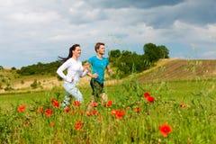 夫妇跑步的外部嬉戏年轻人 免版税库存图片