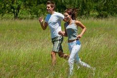 夫妇跑步的草甸夏天年轻人 图库摄影