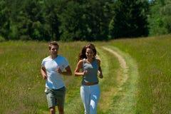 夫妇跑步的草甸夏天年轻人 库存图片