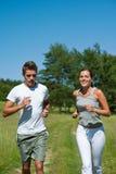 夫妇跑步的草甸嬉戏春天 免版税库存图片