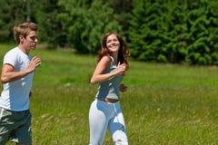 夫妇跑步的草甸微笑的夏天 免版税库存照片