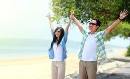 年轻夫妇身分和上升他们的手对天空 免版税图库摄影