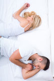 年轻夫妇转动回到彼此在床上 免版税库存图片