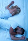 年轻夫妇转动回到彼此在床上 免版税库存照片