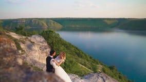 夫妇轻轻地拥抱站立在峭壁边缘和看在湖 股票视频