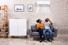 夫妇运行的空调在家 免版税图库摄影