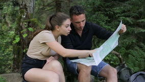 年轻夫妇远足者在寻找路线图的森林 股票视频