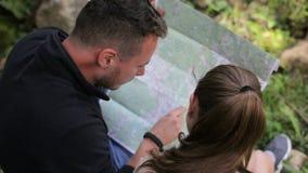 年轻夫妇远足者在寻找路线图的森林 股票录像