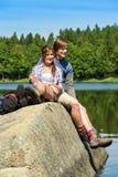 年轻夫妇远足者lounging在湖自然 免版税库存照片