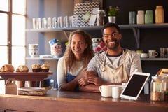 夫妇连续咖啡店画象在柜台后的 免版税库存照片