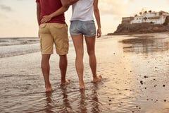 夫妇逗人喜爱的后侧方在海滩的 免版税库存图片