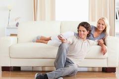夫妇逗人喜爱笑的电视注意 免版税库存图片