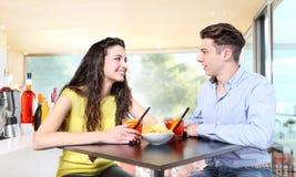 年轻夫妇遇见在饮料的酒吧一个鸡尾酒 库存照片