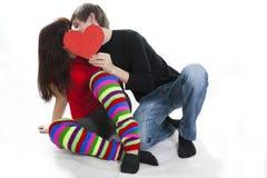 夫妇重点隐藏的亲吻红色他们的年轻&# 库存图片