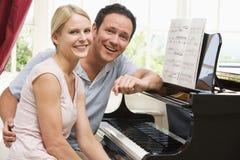 夫妇钢琴坐的微笑 免版税库存图片