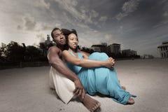 夫妇铺沙坐的年轻人 库存照片