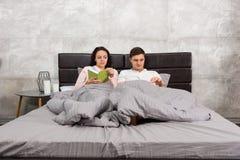 年轻夫妇阅读书,当在床和佩带的pa上时 图库摄影