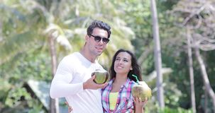 夫妇饮料椰子鸡尾酒谈话在棕榈树、愉快的微笑的人和妇女游人通信 股票录像