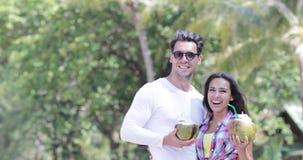 夫妇饮料椰子鸡尾酒谈话在棕榈树、愉快的微笑的人和妇女游人通信 股票视频
