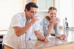 夫妇饮用的厨房牛奶 免版税库存照片