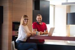 夫妇饮用的咖啡和在家使用膝上型计算机 免版税库存照片