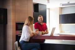 夫妇饮用的咖啡和在家使用膝上型计算机 免版税库存图片