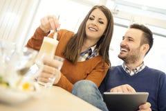 夫妇饮用的咖啡和聊天在咖啡馆 免版税库存图片
