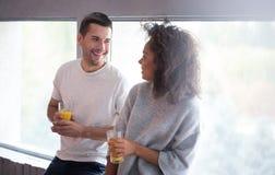 年轻夫妇饮用的汁液和一起笑 免版税库存照片