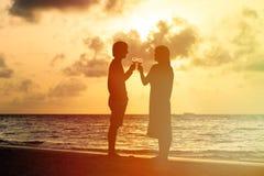 夫妇饮用的酒剪影在日落海滩的 免版税库存照片