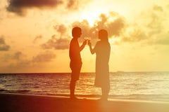 夫妇饮用的酒剪影在日落的 库存图片