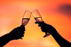 夫妇饮用的香槟剪影在日落的 免版税图库摄影