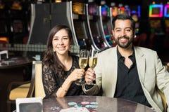 夫妇饮用的香槟在赌博娱乐场 免版税库存图片