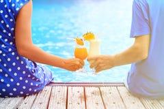 夫妇饮用的鸡尾酒临近水池或海滩 免版税库存照片
