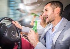 夫妇驾驶喝与汽车 免版税库存图片
