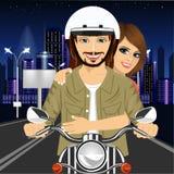 年轻夫妇骑马摩托车通过城市街道在晚上 库存照片