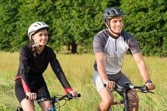 年轻夫妇骑马自行车在草甸 免版税库存图片