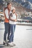 夫妇,女孩和男孩滑冰室外在溜冰场 库存图片
