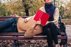 夫妇读书和放松在公园 库存图片
