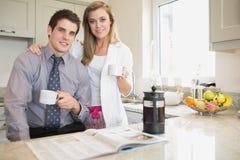 夫妇读书报纸和饮用的咖啡 图库摄影