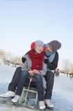 年轻夫妇滑冰,坐冰雪撬 库存照片