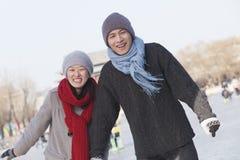 年轻夫妇滑冰,坐冰雪撬 免版税库存图片